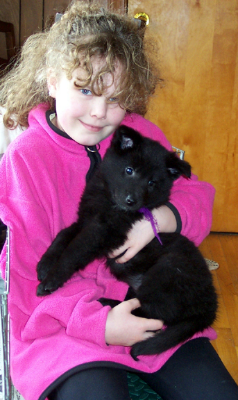 8 1/2 years old, holding a Belgian puppy